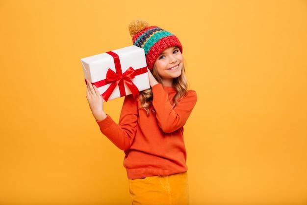 Souriante jeune fille en pull et chapeau tenant une boîte-cadeau et regardant la caméra sur orange