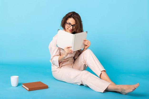 Souriante jeune fille en pyjama home wear posant avec des livres tout en se reposant à la maison isolé sur bleu
