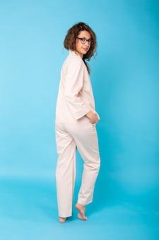 Souriante jeune fille en pyjama home wear posant tout en se reposant à la maison isolé sur mur bleu