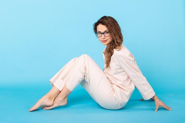 Souriante jeune fille en pyjama home wear posant tout en se reposant à la maison isolée sur fond bleu portrait en studio. détendez-vous concept de mode de vie de bonne humeur.