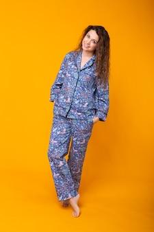 Souriante jeune fille en pyjama home wear posant tout en se reposant à la maison isolée sur fond jaune portrait en studio. détendez-vous concept de mode de vie de bonne humeur.