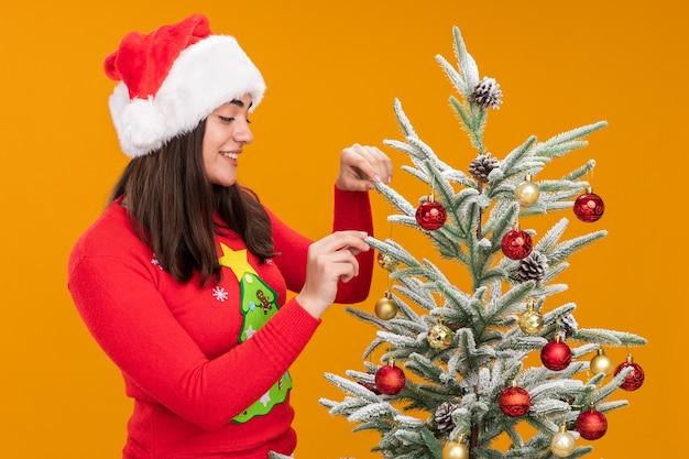 Souriante jeune fille de race blanche avec bonnet de noel debout à côté de l'arbre de noël et la décoration avec des jouets isolés sur fond orange avec espace copie