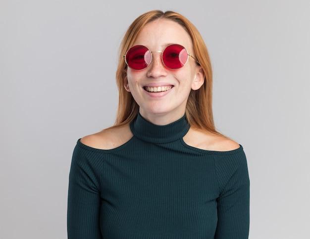 Souriante jeune fille rousse au gingembre avec des taches de rousseur dans des lunettes de soleil regardant la caméra sur blanc