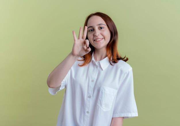 Souriante jeune fille rousse montrant le geste okey sur vert olive