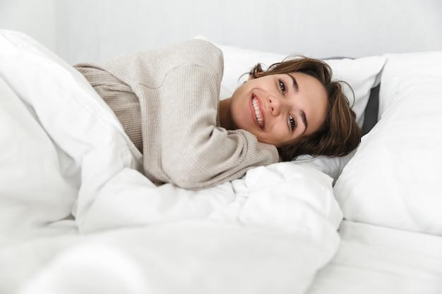 Souriante jeune fille se détendre dans son lit le matin