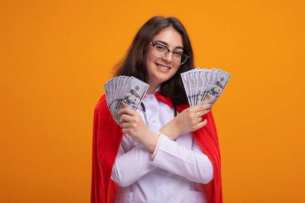 Souriante jeune fille de super-héros caucasienne portant un uniforme de médecin et un stéthoscope avec des lunettes en gardant les mains croisées tenant de l'argent