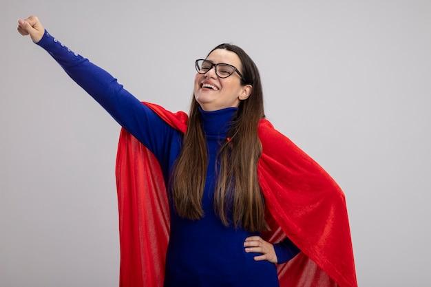 Souriante jeune fille de super-héros portant des lunettes levant le poing isolé sur blanc