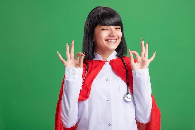 Souriante jeune fille de super-héros portant un stéthoscope avec une robe médicale et une cape montrant le geste correct isolé sur vert