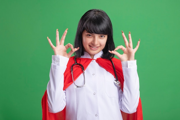 Souriante jeune fille de super-héros portant un stéthoscope avec une robe médicale et une cape montrant des gestes corrects isolés sur vert