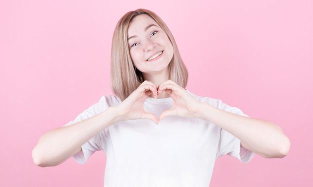 Souriante jeune fille en t-shirt blanc montrant le cœur à deux mains, signe d'amour. concept pour la saint-valentin isolé sur fond rose.