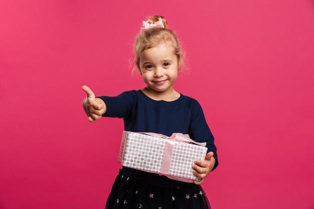 Souriante jeune fille tenant une boîte-cadeau et montrant le pouce vers le haut