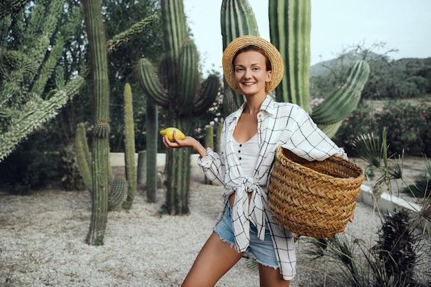 Souriante jeune fille tenant un panier de citrons frais à la ferme parmi les cactus géants verts