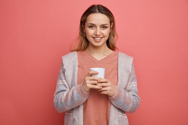 Souriante jeune fille tenant une tasse de thé à deux mains