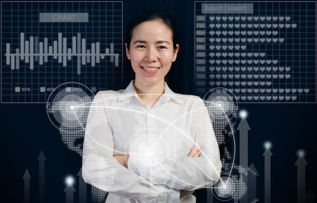 La souriante jeune fille tendance asiatique se croise les bras sur des rapports et des graphiques virtuels.