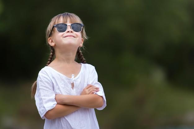 Souriante jeune fille avec des tresses blondes en robe blanche