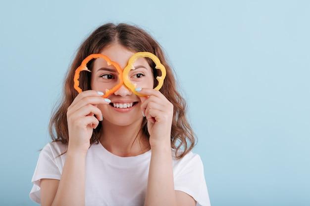 Souriante jeune fille avec des verres de poivre