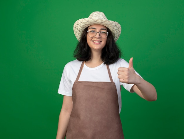 Souriante jeune jardinière brune à lunettes optiques et uniforme portant chapeau de jardinage pouces vers le haut isolé sur mur vert