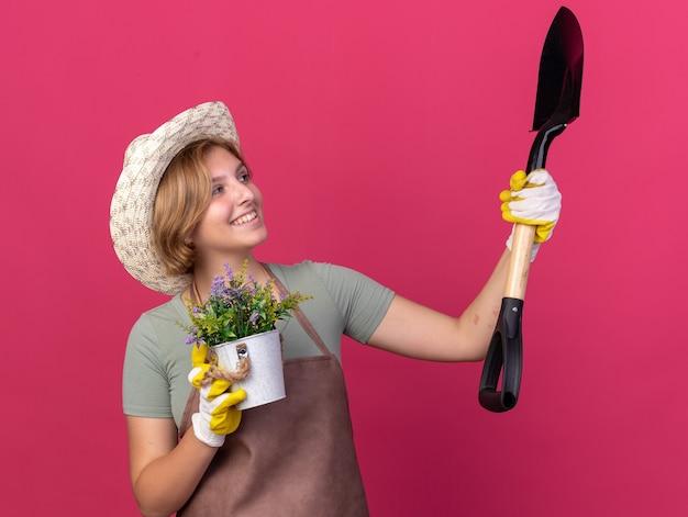 Souriante jeune jardinière slave portant un chapeau de jardinage et des gants tenant des fleurs dans un pot de fleurs et regardant une pelle isolée sur un mur rose avec un espace pour copie