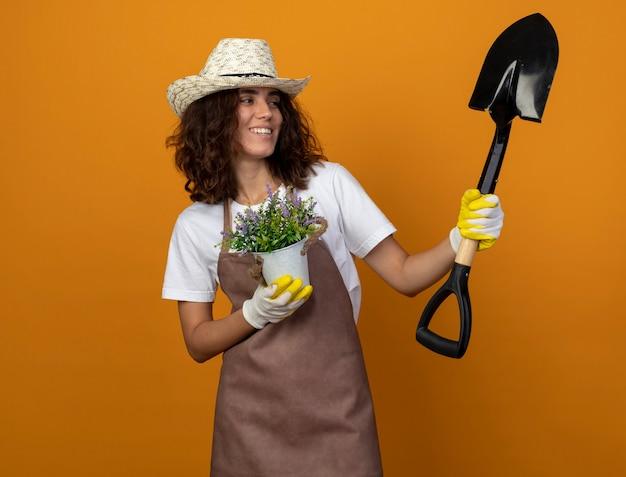 Souriante jeune jardinière en uniforme portant chapeau de jardinage et gants tenant une fleur en pot de fleurs et regardant la pelle dans sa main