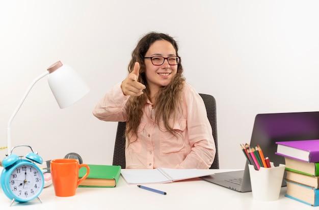 Souriante jeune jolie écolière portant des lunettes assis au bureau avec des outils scolaires à faire ses devoirs pointant vers l'avant et un clin d'oeil isolé sur mur blanc