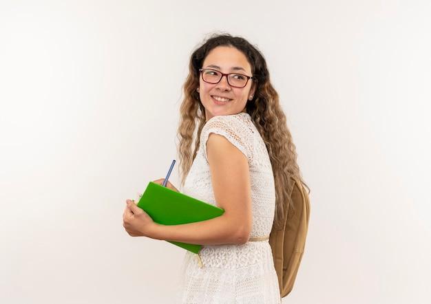 Souriante jeune jolie écolière portant des lunettes et sac à dos debout en vue de profil tenant un livre et un stylo à côté isolé sur mur blanc