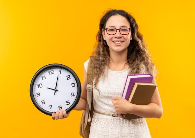 Souriante jeune jolie écolière portant des lunettes et sac à dos tenant horloge et livres isolés sur mur jaune