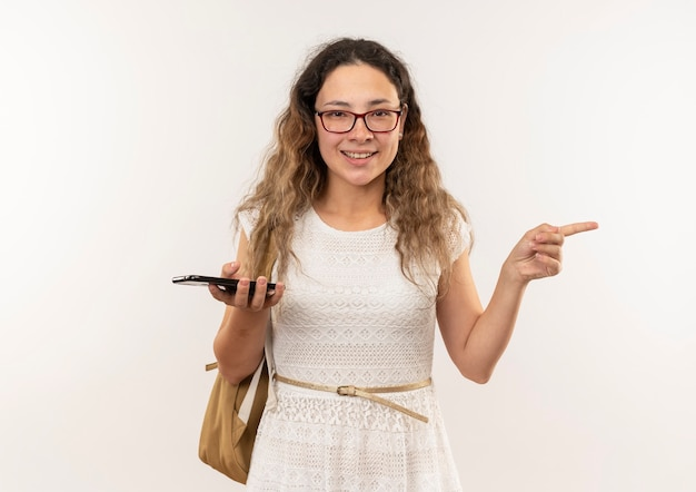 Souriante jeune jolie écolière portant des lunettes et sac à dos tenant un téléphone mobile pointant sur le côté isolé sur le mur