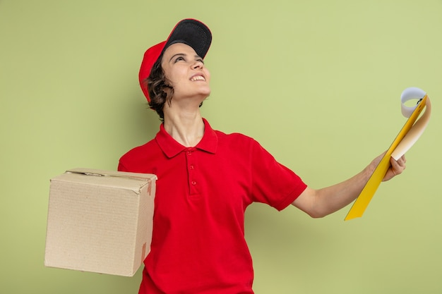 Souriante jeune jolie femme de livraison tenant une boîte en carton et un presse-papiers en levant