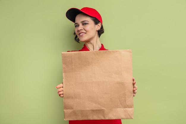 Souriante jeune jolie femme de livraison tenant des emballages alimentaires en papier