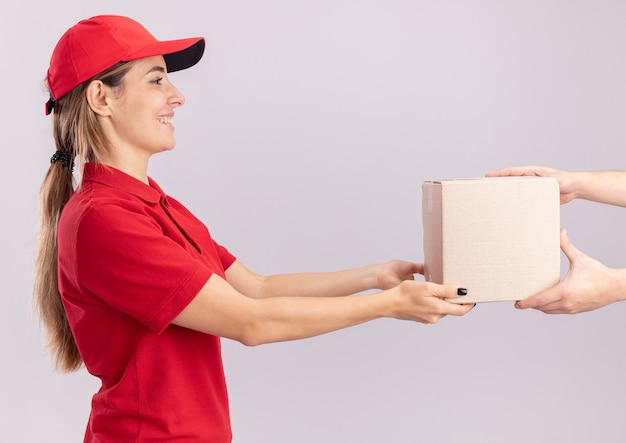 Souriante jeune jolie femme de livraison en uniforme donne carton à quelqu'un isolé sur mur blanc