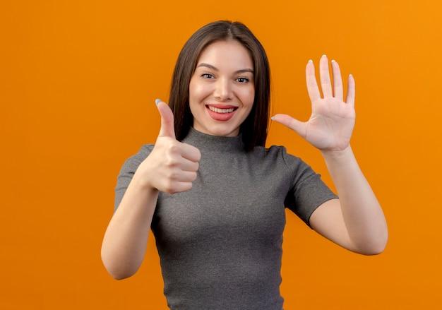 Souriante jeune jolie femme montrant le pouce vers le haut et cinq avec la main isolé sur fond orange