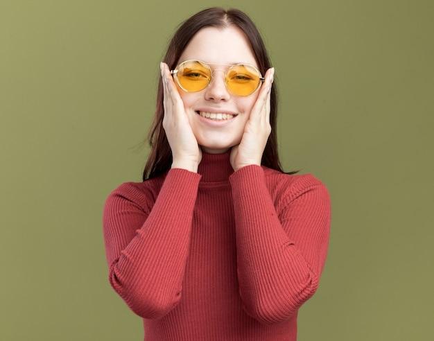 Souriante jeune jolie femme portant des lunettes de soleil gardant les mains sur le visage regardant devant isolé sur un mur vert olive
