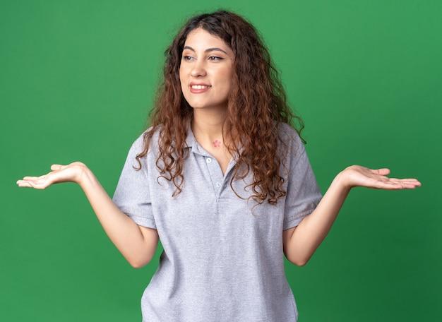 Souriante jeune jolie femme regardant le côté montrant les mains vides isolées sur le mur vert