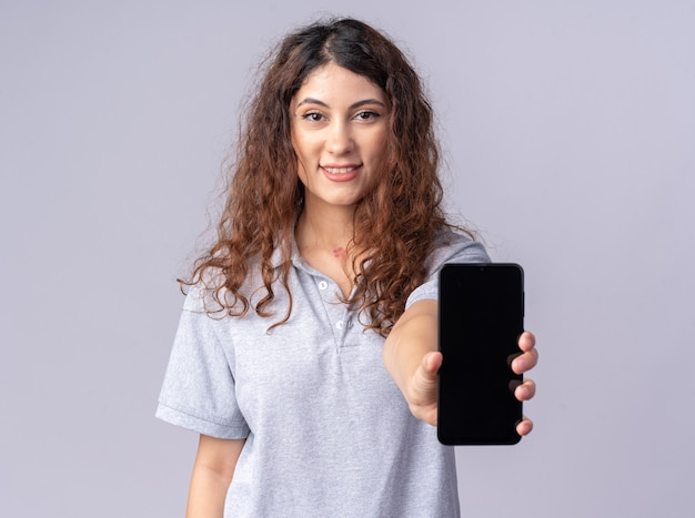 Souriante jeune jolie femme regardant devant étirant le téléphone portable vers l'avant isolé sur mur blanc