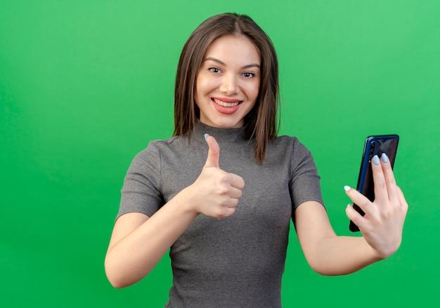 Souriante jeune jolie femme tenant un téléphone mobile et montrant le pouce vers le haut isolé sur fond vert