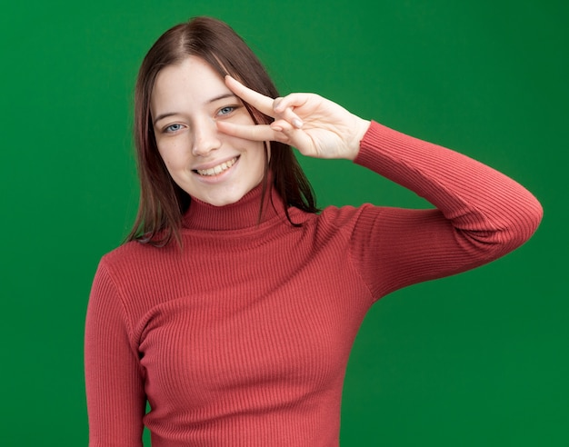 Souriante jeune jolie fille montrant le symbole v-signe près de l'œil isolé sur mur vert