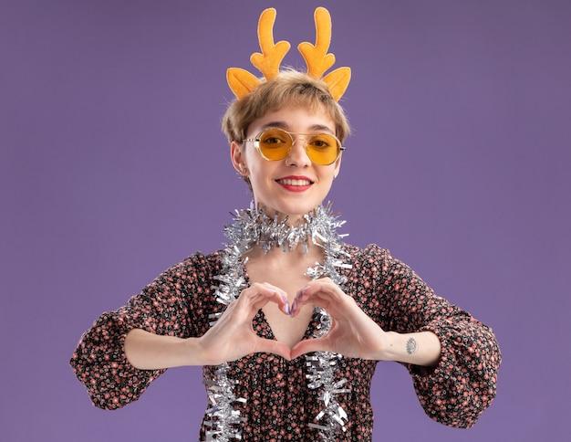 Souriante jeune jolie fille portant bandeau de bois de renne et guirlande de guirlandes autour du cou avec des lunettes regardant la caméra faisant signe de coeur isolé sur fond violet