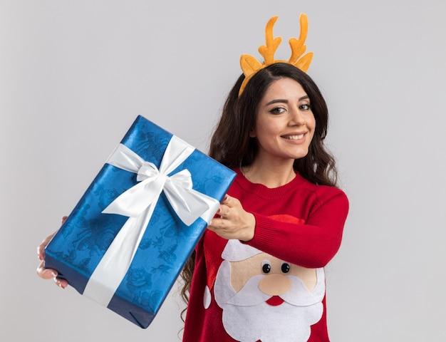 Souriante jeune jolie fille portant un bandeau de bois de renne et un pull du père noël qui s'étend de l'emballage cadeau de noël vers la caméra à la recherche