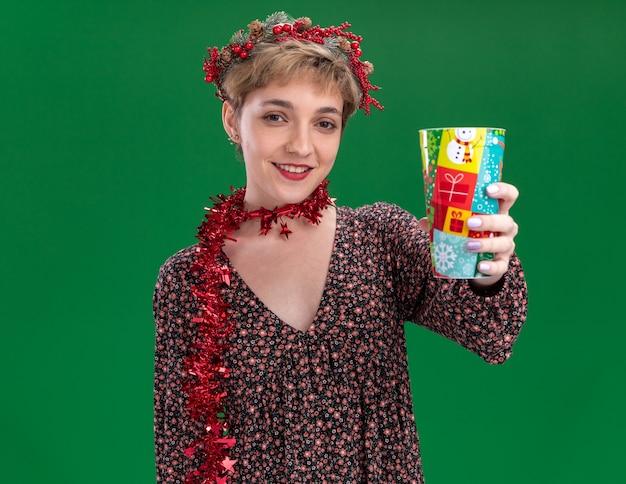 Souriante jeune jolie fille portant couronne de tête de noël et guirlande de guirlandes autour du cou qui s'étend de la tasse de noël en plastique vers la caméra regardant la caméra isolée sur fond vert