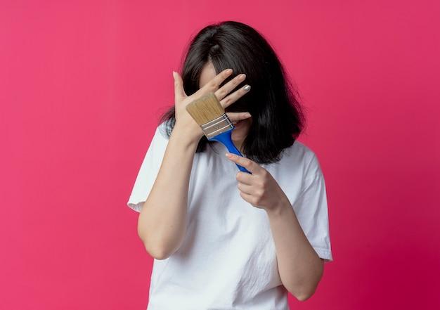 Souriante jeune jolie fille tenant un pinceau et se cachant le visage derrière la main