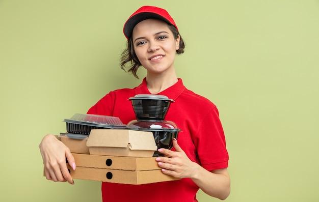 Souriante jeune jolie livreuse tenant des contenants de nourriture et des emballages sur des boîtes à pizza