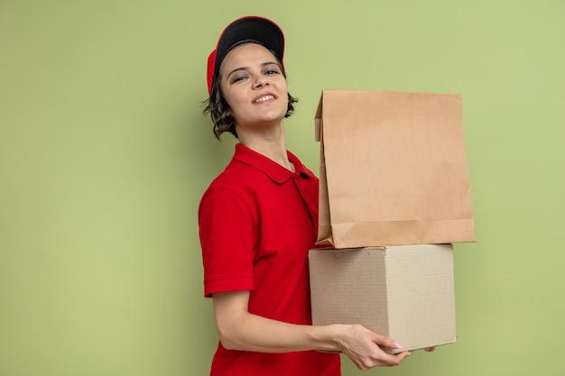 Souriante jeune jolie livreuse tenant un emballage alimentaire en papier et une boîte en carton
