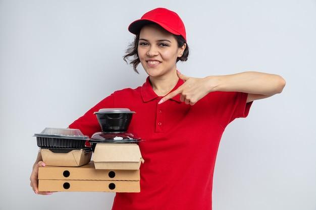 Souriante jeune jolie livreuse tenant et pointant des récipients alimentaires avec emballage sur des boîtes à pizza