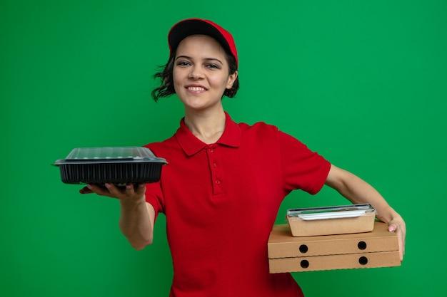 Souriante jeune jolie livreuse tenant un récipient de nourriture et un emballage sur des boîtes à pizza