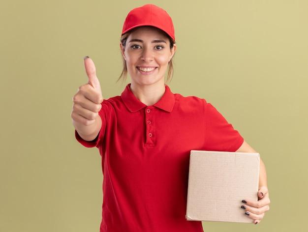 Souriante jeune jolie livreuse en uniforme pouces vers le haut et détient une boîte en carton sur vert olive