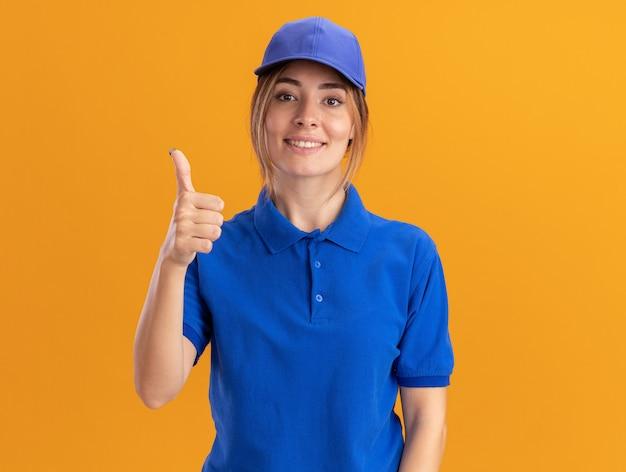 Souriante jeune jolie livreuse en uniforme pouces vers le haut sur orange