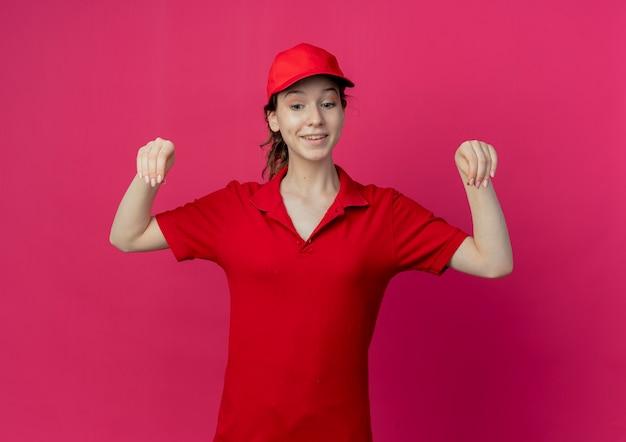 Souriante Jeune Jolie Livreuse En Uniforme Rouge Et Capuchon Regardant Vers Le Bas Et Faire Semblant De Tenir Quelque Chose D'isolé Sur Fond Cramoisi Photo gratuit