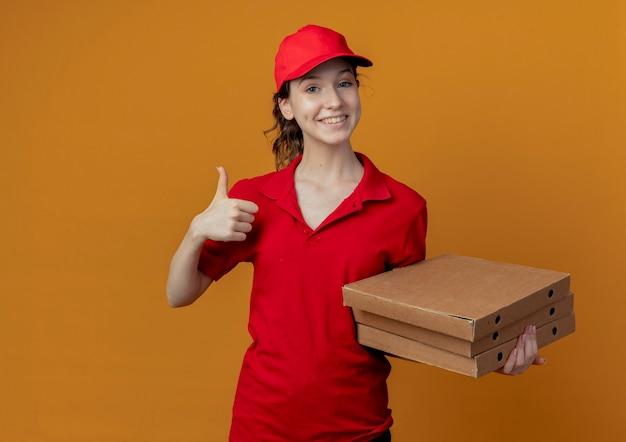 Souriante jeune jolie livreuse en uniforme rouge et capuchon tenant des paquets de pizza et montrant le pouce vers le haut isolé sur fond orange avec espace de copie