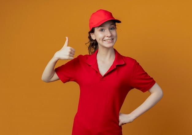 Souriante jeune jolie livreuse en uniforme rouge et casquette mettant la main sur la taille et montrant le pouce vers le haut isolé sur fond orange avec espace de copie