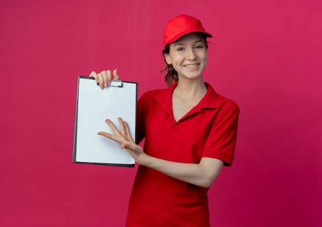 Souriante jeune jolie livreuse en uniforme rouge et casquette montrant le presse-papiers et pointant avec la main sur elle isolé sur fond cramoisi avec espace de copie